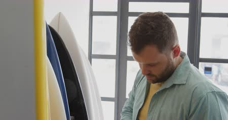 vocação : Front view close up of a millennial Caucasian male surfboard maker in his studio, inspecting surfboards standing in a rack and turning to camera and smiling