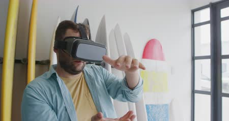 vocação : Front view close up of a millennial Caucasian male surfboard maker in his studio, using a VR headset and moving his hands in front of him, a rack of surfboards behind him Vídeos