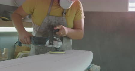 knutselen : Front view of a millennial Caucasian male surfboard maker in his workshop wearing a face mask and polishing a new surfboard with a power tool during the manufacturing process Stockvideo