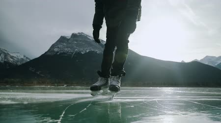 stopping : Front view low section of a millennial man ice skating on a frozen lake, skidding to a halt in front of camera