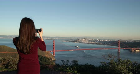 dark bay : Rear view of a young Caucasian woman with long dark hair walking in the Golden Gate National Recreation Area and stopping to take pictures of the Golden Gate Bridge and the San Francisco Bay Area with a smartphone