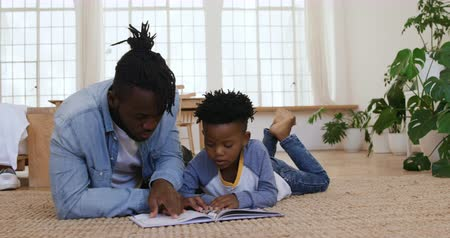 raszta : Front view of a millennial African American man and his young son at home, lying on the floor in their sitting room reading a book together, slow motion Stock mozgókép