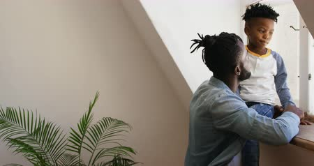 denim : Side view of a millennial African American man standing beside his young son sitting on a window sill while they talk and look out of the window together at home, slow motion
