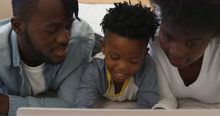 ailelerin : Front view close up of a smiling millennial african american family and their young son lying on a bed together at home using a laptop computer and talking, slow motion