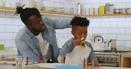 pastelli a cera : Front view of a young african american son and his millennial father sitting at a table at home in their kitchen, the boy playing with crayons while his father untangles his hair Filmati Stock