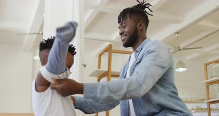 juntar : Side view close up of a smiling millennial african american father helping his young son get dressed at home, slow motion