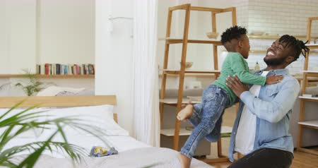 ugró : Side view of a young African American boy standing on a bed at home and jumping into the arms of his millennial father Stock mozgókép