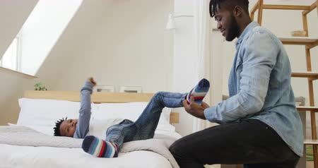 vader en zoon : Side view of a smiling millennial african american father helping his young son put his sock on while he lies on a bed at home, slow motion Stockvideo