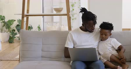 shelf life : Front view of a smiling millennial african american father and his young son at home, sitting on the sofa in their sitting room using a laptop computer together and talking