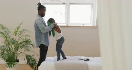svetr : Side view of a millennial african american father helping his young son put on a sweater while he stands on a bed at home, slow motion