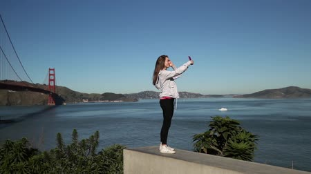 dark bay : Side view of a woman with long dark hair standing using a smartphone and taking selfies with the Golden Gate Bridge and the San Francisco Bay Area in the background, slow motion Stock Footage