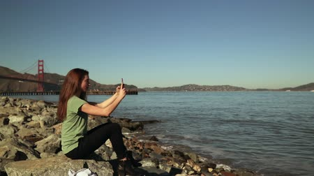 beside : Side view of a woman with long dark hair sitting on rocks beside the water taking selfies using a smartphone with the Golden Gate Bridge and the San Francisco Bay Area in the background, slow motion Stock Footage