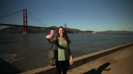 Франциско : Front view of a woman with long dark hair standing and taking selfies using a smartphone, with the Golden Gate Bridge and the San Francisco Bay Area in the background, slow motion