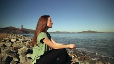 dark bay : Side view close up of a young Caucasian woman with long dark hair sitting on rocks beside the water with the Golden Gate Bridge and the San Francisco Bay Area in the background, slow motion Stock Footage