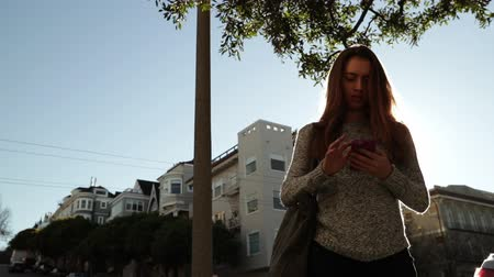 tasje : Front view low angle of a young Caucasian woman with long dark hair standing on a sunny city street using a smartphone and smiling, backlit by sunlight, slow motion