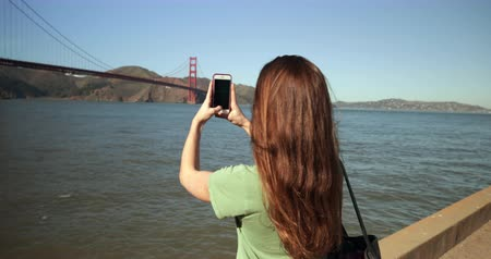 dark bay : Rear view of a young Caucasian woman with long dark hair standing and taking pictures of the Golden Gate Bridge and the San Francisco bay area with a smartphone, looking at her phone and smiling Stock Footage