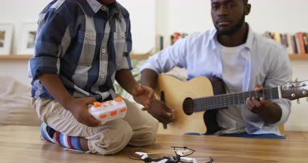 ahize : Front view close up of a millennial african american father and his young son at home together, the father playing an acoustic guitar, while his young son sits on the table holding a handset and playing with a mini drone, slow motion