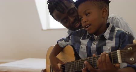 négy : Side view close up of a young African American boy playing an acoustic guitar at home with his millennial father sitting behind him helping and listening, slow motion