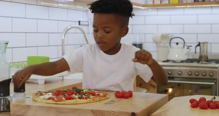 avantajado : Front view close up of a smiling millennial african american father and his young son preparing food together in the kitchen at home and talking, the father chopping vegetables and his son putting topping and herbs on a pizza base, slow motion Stock Footage