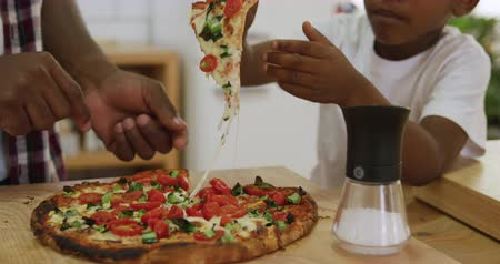 placa : Front view mid section of a millennial african american father and his young son preparing food together in the kitchen at home, the son taking the first slice of a pizza they baked to eat, slow motion
