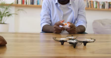 ahize : Front view of a millennial african american father and his young son at home together, the father using a handset and controlling a mini drone on the table with the hands of his son pointing to it slow motion