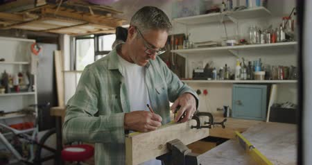 do it yourself : Front view of a Caucasian man wearing glasses doing DIY in a workshop at home, measuring a piece of wood clamped in a vice with a tape measure and marking it with a pencil, slow motion Stock Footage
