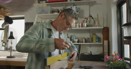 do it yourself : Side view of a Caucasian man wearing glasses doing DIY in a workshop at home, measuring a piece of wood in a vice and marking it with a pencil, slow motion Stock Footage