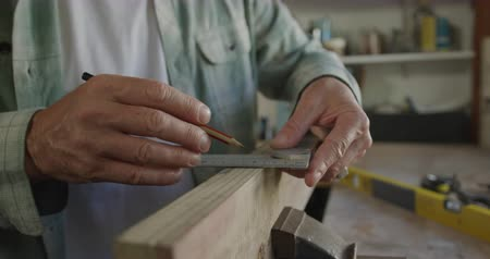 do it yourself : Side view mid section of a Caucasian man doing DIY in a workshop at home, measuring with a set square and marking a piece of wood clamped in a vice with a pencil, slow motion Stock Footage