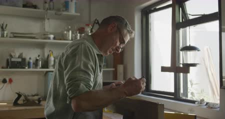 teszi : Side view close up of a Caucasian man wearing glasses standing by a window doing DIY in a workshop at home, measuring a piece of wood clamped in a vice and marking it with a pencil, slow motion