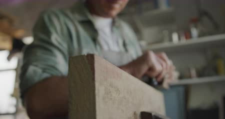 teszi : Side view mid section of a Caucasian man doing DIY in a workshop at home, planing a piece of wood clamped in a vice, slow motion Stock mozgókép