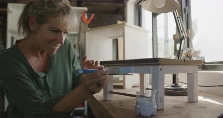 faca : Side view close up of a smiling Caucasian woman doing DIY in a workshop at home, painting a small stool, slow motion