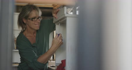 faca : Front view of a Caucasian woman wearing glasses doing DIY in a workshop at home, using a screwdriver and assembling a piece of furniture, slow motion