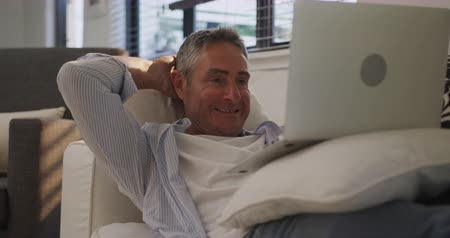 reclináveis : Front view close up of a smiling Caucasian man using a laptop computer at home reclining on a sofa, with the sun shining through a window behind him, slow motion Vídeos