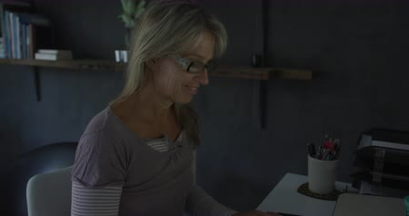 night life : Side view close up of a happy Caucasian woman wearing glasses using a desktop computer at home sitting at a desk at night, typing and looking at the monitor, slow motion Stock Footage