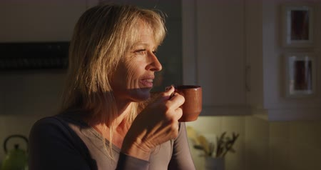 trabalhos domésticos : Side view close up of a Caucasian woman drinking a cup of coffee at home, standing in her kitchen, looking straight ahead and smiling, with the sun shining on her face, slow motion