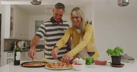 grated : Front view of a happy adult Caucasian couple standing at home in their kitchen preparing pizzas together, topping them with grated cheese and smiling, slow motion Stock Footage