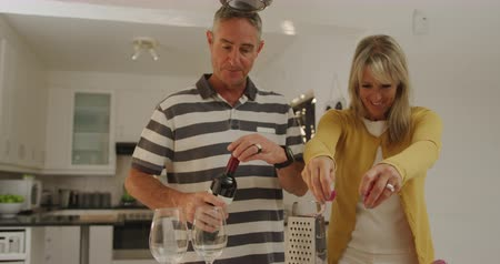 köret : Front view of a happy adult Caucasian couple standing at home in their kitchen preparing a meal together, the woman sprinkling a garnish on food and the man pouring glasses of red wine, slow motion