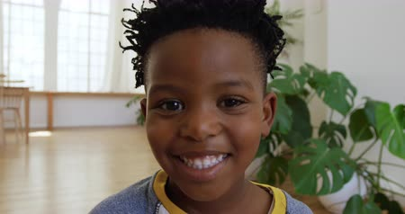 rövid : Portrait close up of a cute young African American boy at home in his sitting room smiling to the camera