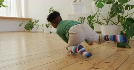 ugró : Front view of a cute young African American boy spinning around on the wooden floor at home having fun, slow motion Stock mozgókép