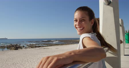 hajló : Side view of a happy young Caucasian woman sitting on sunny beach leaning on a fence with her arms stretched out, turned to camera smiling, slow motion