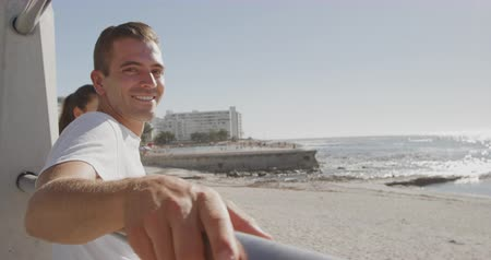 turning off : Side view of a happy young Caucasian man sitting on sunny beach leaning on a fence with his arms stretched out, turning to camera and smiling, slow motion