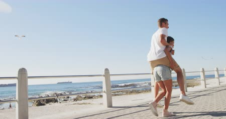 проведение : Rear view of a happy young adult Caucasian couple piggybacking by the sea, the young woman carrying the man on her back, slow motion
