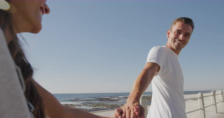pulling off : Side view of a happy young adult Caucasian couple by the sea, walking hand in hand and smiling to each other, the woman close to camera in the foreground, slow motion Stock Footage