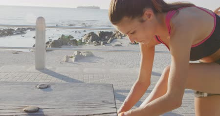 cipőfűző : Front view close up of a young Caucasian woman in sportswear standing with her foot up on a bench, tying her shoelace before a run on a sunny day by the sea Stock mozgókép