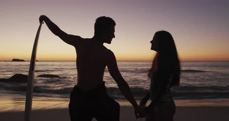 hajló : Side view of a happy young adult Caucasian couple standing by the sea kissing, silhouetted against the sunset, the man leaning on a surfboard, slow motion Stock mozgókép