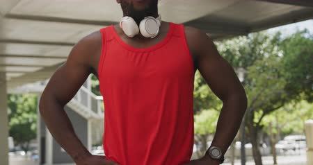 focussed : Front view close up of an athletic African American man in sportswear with headphones around his neck taking a break under a bridge while training on a sunny day in the city, slow motion