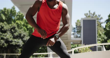 squatting : Front view of an athletic African American man in sportswear squatting and stretching under a bridge while training on a sunny day in the city, slow motion Stock Footage