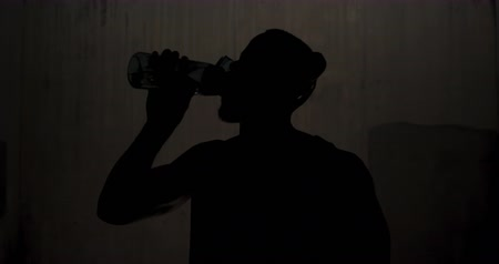 focussed : Front view of the silhoutte of an athletic African American man taking a break, leaning against a wall and drinking water under a bridge while training on a sunny day in the city, slow motion