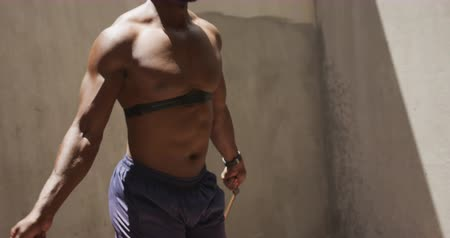 skákání : Side view close up of a shirtless African American man wearing a chest strap heart rate monitor and skipping with a rope in the shade under a bridge, while exercising on a sunny day in the city, slow motion