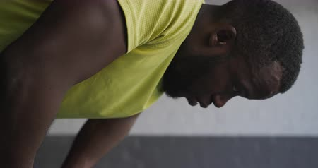 recovering : Side view close up of an athletic African American man in sportswear resting in an underpass during exercise on a sunny day in the city, slow motion Stock Footage